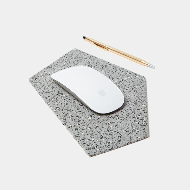A grey and white speckled, abstract, pentagon shaped mousepad sits in the middle of a plain white background. A crisp, white, apple magic mouse sits in the center of the mouse pad. To the right lays a sleek gold ballpoint pen.