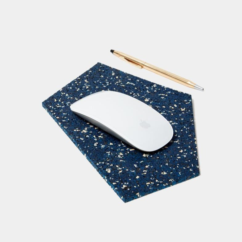 A blue, black and white speckled pentagon shaped mousepad sits in the foreground. Atop is one crisp, clean, brand new magic mouse. To the right lays a gold ballpoint pen. This person is ready to work. This person is you.