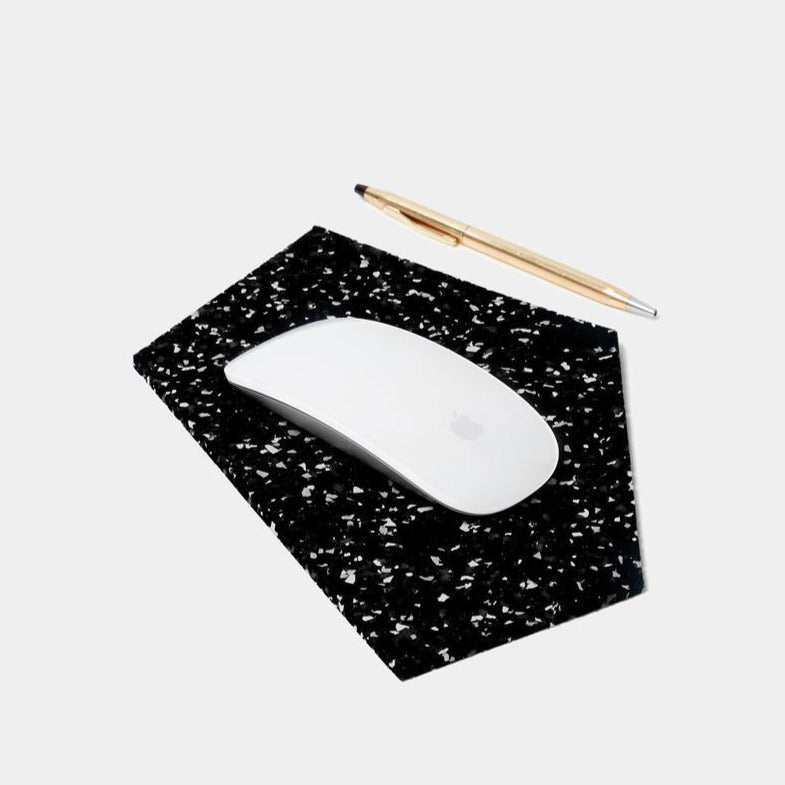 A flat, black and white speckled, abstract pentagon shaped mouse pad sits in the foreground, underneath a crisp white apple magic mouse. To the right sits a single, slender, sleek, golden pen. Very smooth, very sleek, clean lines here. Are you an architect? With this mouse pad, you could pass for one.