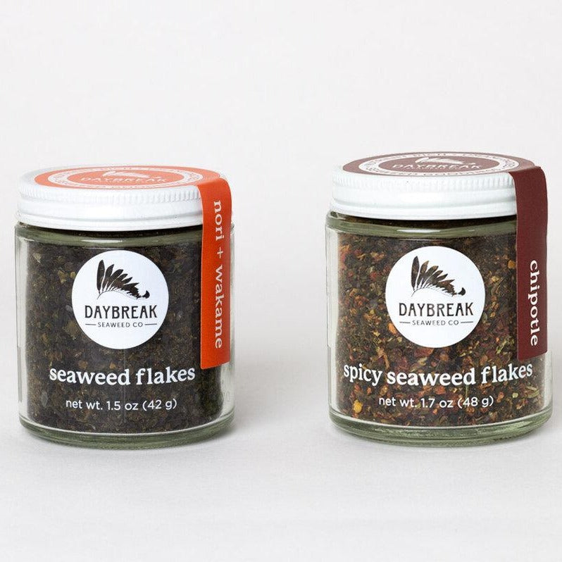 Two glass jars sit side by side filled with two different kinds of seaweed flakes. The left jar is full of dark seeweed flakes with an orange label that reads nori & wakame. The right jar is full of clear and dark flakes with a navy label down the side that reads wakame and sea salt.