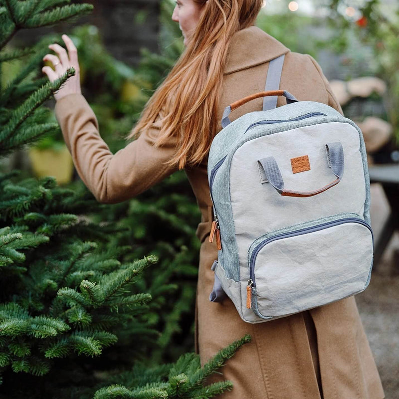 A grey cooler backpack (made sustainably from paper!) is shown on the back of a woman with long red hair, wearing a camel brown winter coat. She is extending her arm out to touch a christmas or evergreen tree. It is cold out, but she is still using her cooler backpack to hold her accessories and laptop. It's great for all seasons and looks handsome with her outfit.