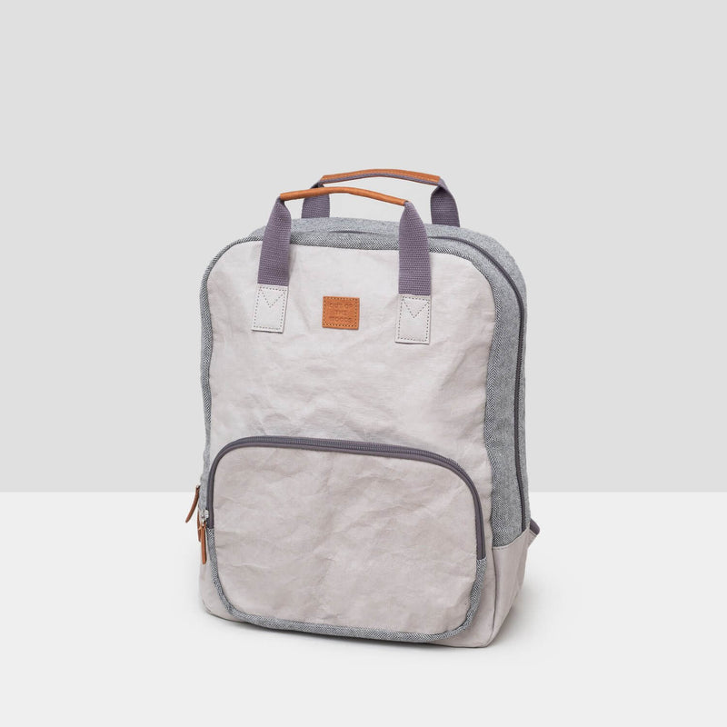 A light grey cooler backpack sits on a grey background. It has dark grey short top straps that are floating vertically with saddle brown accents at top of the straps and at the zipper pulls. The bag unzips at the top and there is also a zippered front pocket. The bag is sustainable and made from paper. It is easy to carry with comfortable, wide, cotton straps -- the perfect accompaniment to a park or beach picnic!