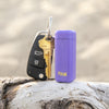 Here, one can see a bright purple collapsible straw holding case, with a yellow Final. logo near it's bottom, sitting on a log. The case is attached to a key ring with a black car key and gold house key attached. The keys and straw case measure 5 or so inches in height.
