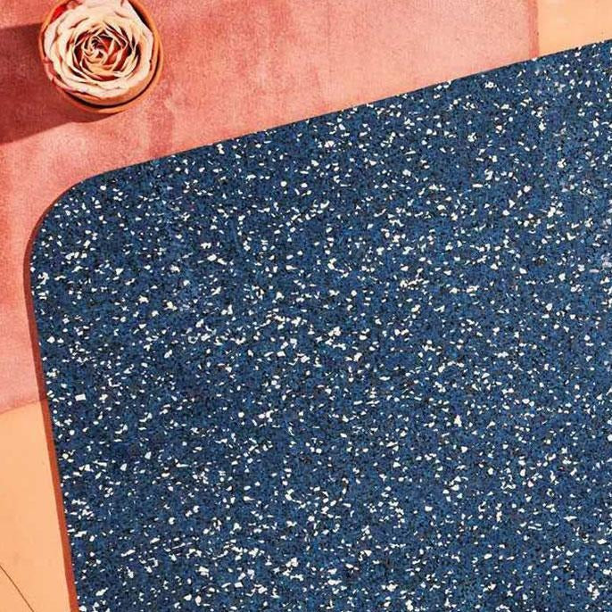Close up of the royal blue speckled recycled rubber terrazzo material of this sustainable WFH ready desk mat.
