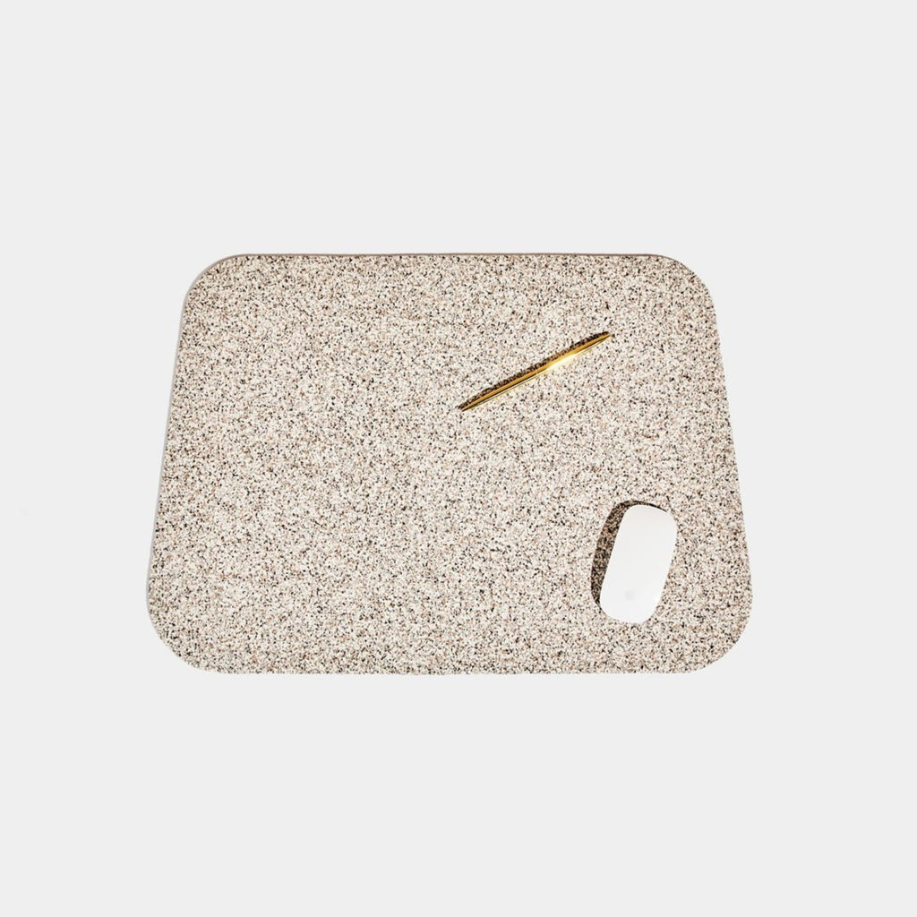Speckled beige terrazzo deskmat with rounded edges. It's made of a super sustainable recycled rubber material by hand in the US.