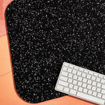 Close up of the black speckled recycled rubber terrazzo material of this sustainable WFH ready desk mat and wireless keyboard.