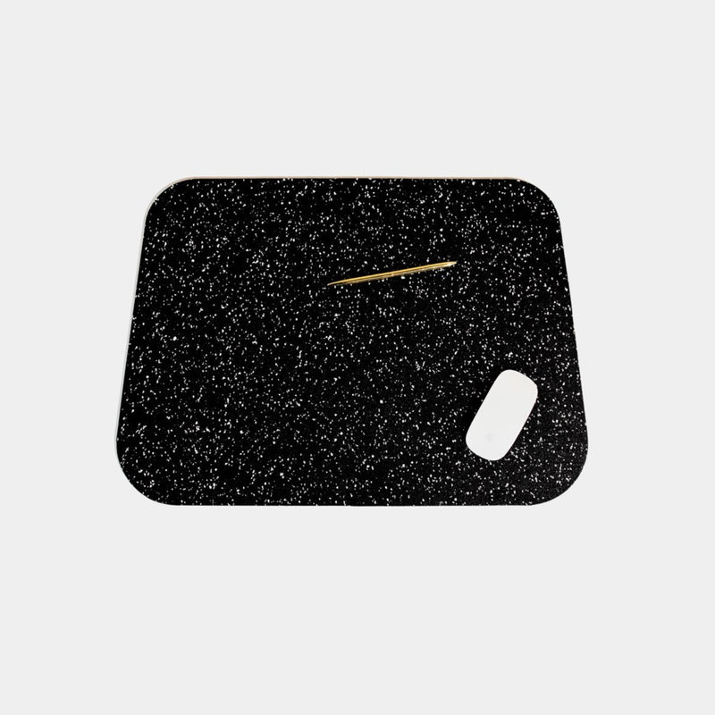 Speckled black terrazzo deskmat with rounded edges. It's made of a super sustainable recycled rubber material by hand in the US.