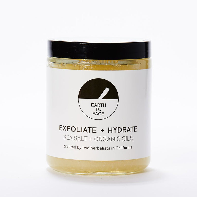 Though this looks like a small jar of honey, this reusable and recyclable glass jar (pictured in in the center of this white background) is filled with a delightful blend of sea salt and organic oils, ready to gently exfoliate and hydrate your body. The white branded label wraps the jar, and it's sealed with a black lid.