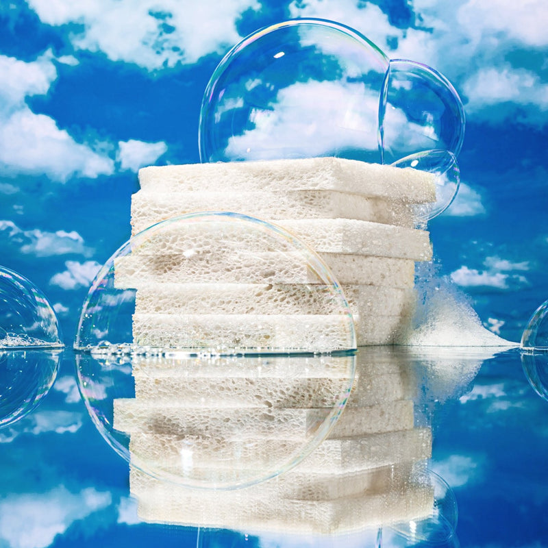 In the middle of the image, a stack of 6 plastic-free sponges sit towering and artfully arranged on top of one another. Each sponge is 100% plant-based and made from natural wood pulp with zero plastic or dyes. The stack of sponges sits on a glassy water surface that reflects an image of the sponges and the blue sky above with fluffy white clouds. There are large magical soap bubbles clinging to the sponges. The scene is serene, calming, and euphorically clean.
