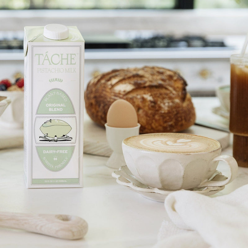 A white and pistachio colored tetrapak of shelf stable pistachio milk sits on a counter next to an enviable spread of breakfast foods and a beautiful cappucino in a bespoke white teacup.