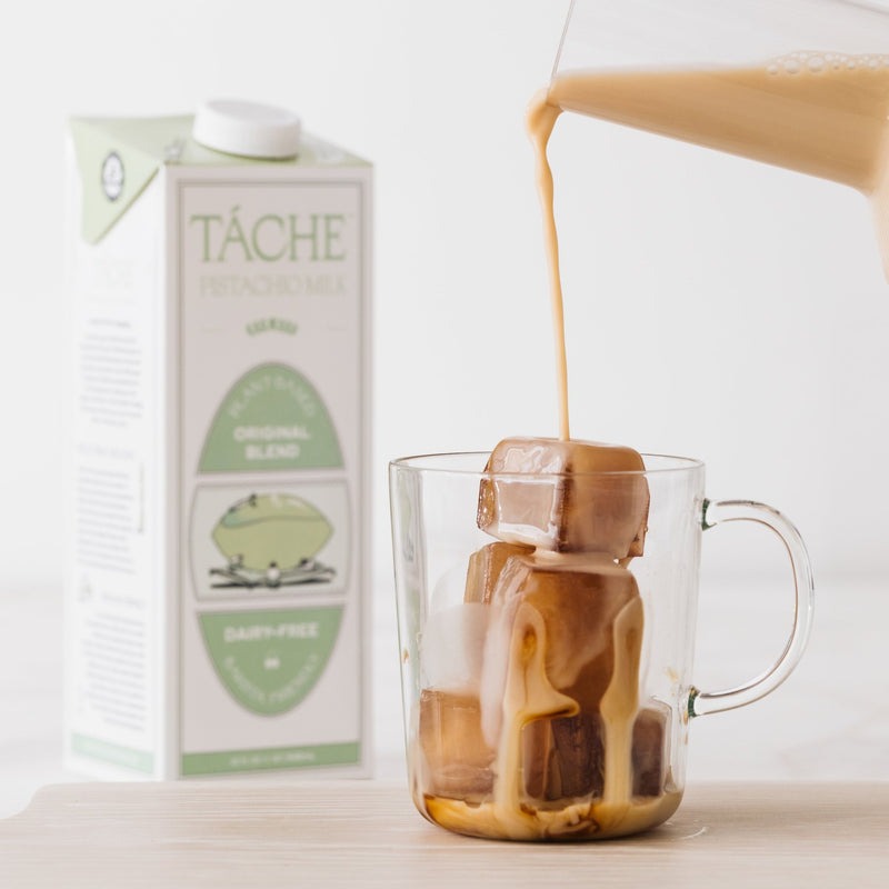 A delicious pistachio milk is getting poured over some beautiful cold brew ice cubes in a clear mug. You can see the Tache pistachio milk container in the background but the coffee looks so good, it'll steal your focus.