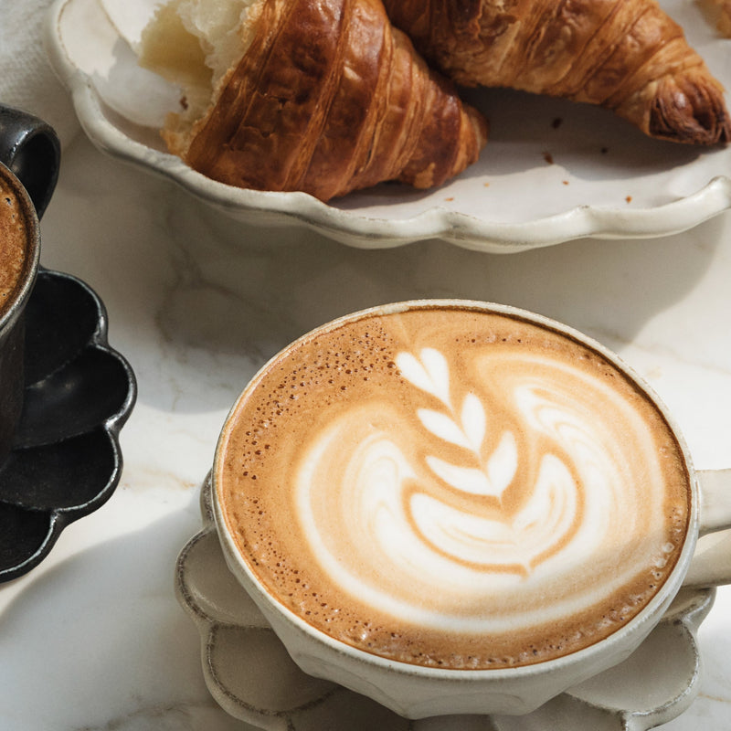 Looking for proof that pistachio milk will foam and steam like a dream? Look no further-- here some beautiful latte art tops a white mug full of delicious coffee, artfully placed next to a tray of croiisants.