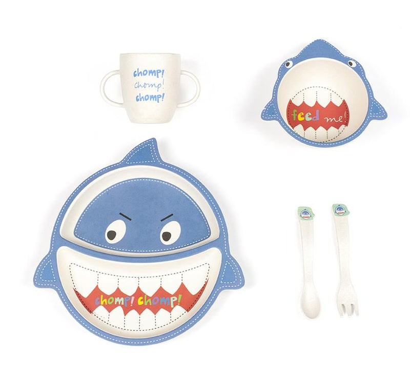 A children's dinner set is shown against a plain white background. The right side features a shark shaped bowl in the upper corner while a fork and knife set is shown in the lower corner. The left side has a children's cup in the upper portion and a shark shaped plate in the lower corner. All four items are sustainably made from bamboo and are fully biodegradable.