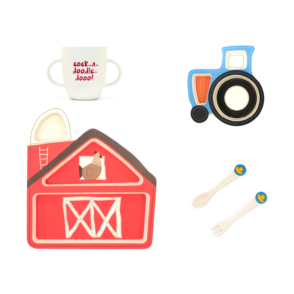 "A dinner set made for children is shown in this image. A red plate made to look like a barn is in the left bottom corner while in the left upper corner a white cup reads ""cock-a-doodle-doo!"" A fork and a knife set are found in the bottom right corner and a bowl in the shape of a blue tractor is in the right upper corner."
