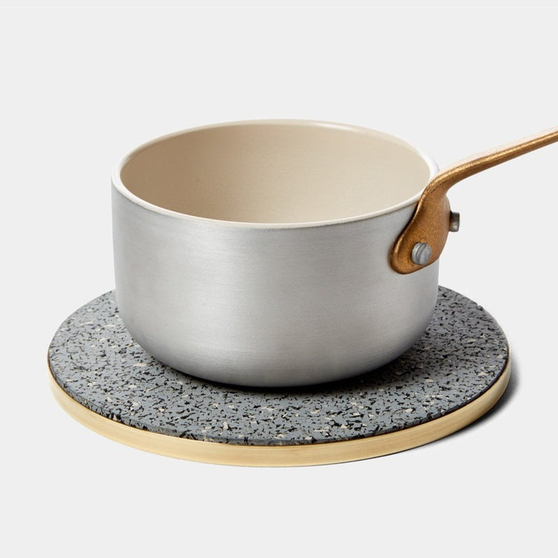 A steel saucepan sits on a recycled rubber trivet with a brass outer. The trivet is slightly larger than the saucepan and is grey and speckled and modern and stylish.