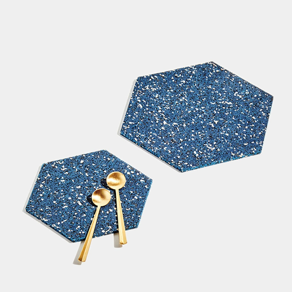 This set of blue hexagonal trivets is made of a super sustainable recycled rubber blend that's zero waste and made by hand in the US. It's texture and materials make it look as though it has a terrazzo pattern.
