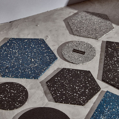 On a grey cement background, a hodge podge of mismatched hexagonal and circular trivets is laid out.
