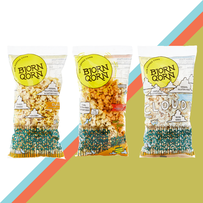 Three large BjornQorn sun-popped corn bags are lined up next to each other. The background is a yellow green large diagonal stripe with a much thinner red and then equally thin blue stripe to the left of the green. The bags are three different flavors: classic, spicy, and salty.