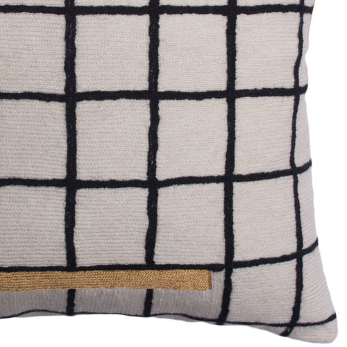 This is a close-up of the sustainable throw pillow with the grid pattern and the gold accent, where you can really see the wool embroidery that's done by hand.