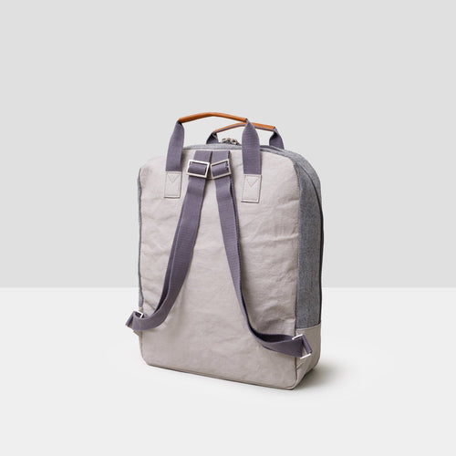 A light grey cooler backpack sits on a grey background. It has dark grey short top straps that are floating vertically with saddle brown accents at top of the straps and at the zipper pulls. The bag is shown from the back, exposing two comfortable, adjustable, cotton backpack straps. It is the perfect accompaniment to a park or beach picnic!