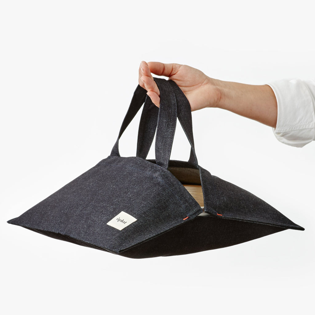 "A denim dish tote is held in the air by a White hand. The tote has an opening in the center and can fit a ""13 round or square dish. Sustainably made in a zero waste factory in California, these measure 15"" x 15"" when flat and empty."