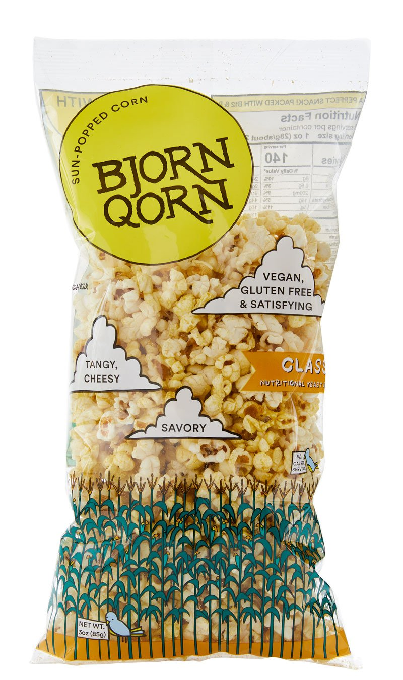 A close-up of the classic BjornQorn sun-popped corn bag reveals a large BjornQorn label and three clouds filled with descriptive words like savory, tangy, vegan, and gluten free. The bottom of the bag is decorated with a row of green corn stalks and a two very small (smaller than a penny) blue birds.