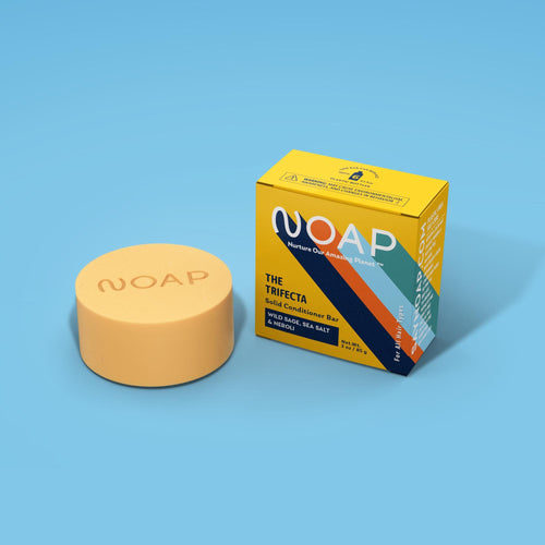 The Wild Sage, Sea Salt & Neroli conditioner bar, which is disc-shaped, next to its yellow box. The disc is pale yellow-cream colored and has the NOAP logo carved into the top surface of the thick disc.
