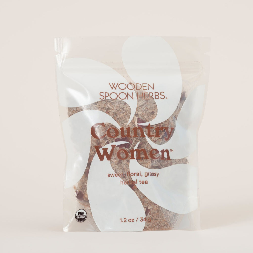 A resealable bag sits in the foreground. Partially transparent, we see a white pinwheel design on the front teasing the medley of aromatic herbs within. 'Country Women--sweet, floral, grassy herbal tea' the label reads. If you're looking for groovy garden herbs, this is for you.