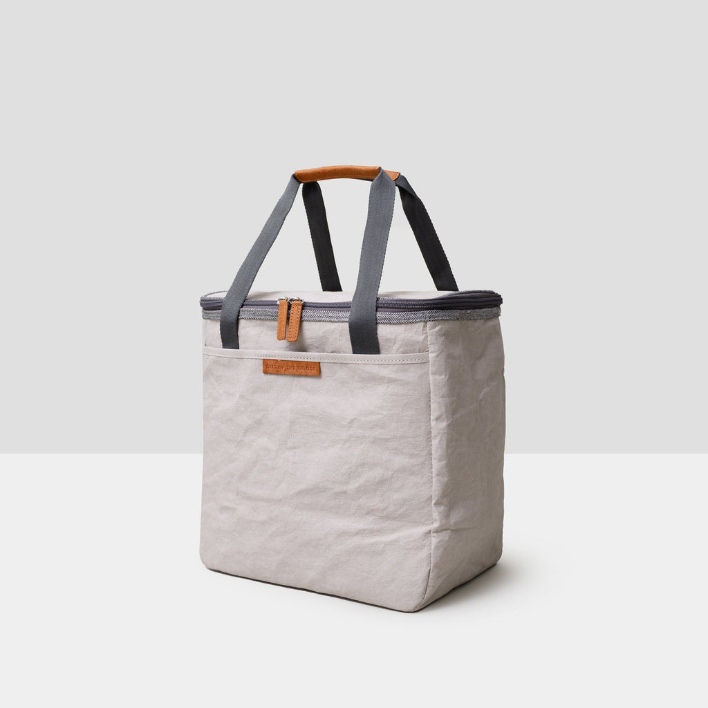A light grey rectangular cooler bag sits on a grey background. It has dark grey straps that are floating vertically and fully extended and saddle brown accents at the zipper pulls and top handles. The bag is sustainable and made from paper. It is both handsome and chic -- the perfect accompaniment to a park or beach picnic!
