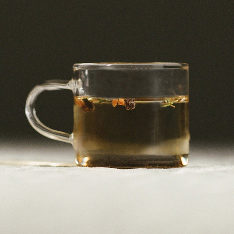 A shallow borosilicate glass mug sits a few feet away, filled with a golden elixir. We can see a few herbs, or maybe flowers, dance along the beverage's surface. It's warm, it's inviting, it's just what the doctor ordered.