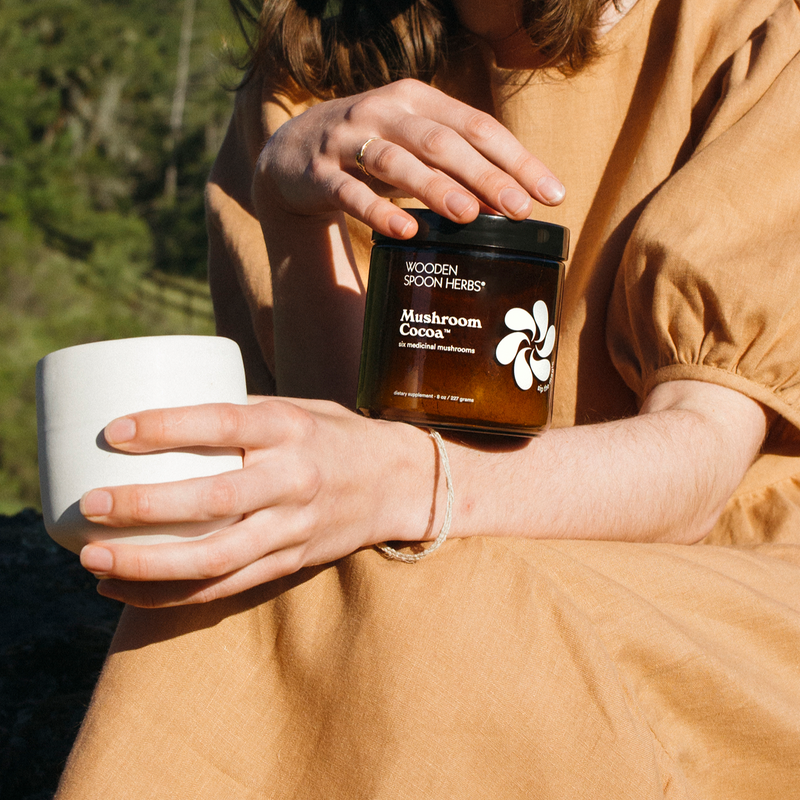 A woman sits in the grass, we see a fence from a nearby farm in the distance. She's wearing an ochre colored linen dress. In one hand, she holds a white ceramic mug, presumably filled with the aforementioned mushroom cocoa mixture. With the other, she's balancing a jar of mushroom cocoa powder on her arm.