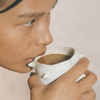 A bronzed young woman sips from a white ceramic handmade mug containing a delicious, adaptogen-filled mushroom cacoa latte. She looks off into the distance, contemplating the bioavailability of the ingredients in her next meal.