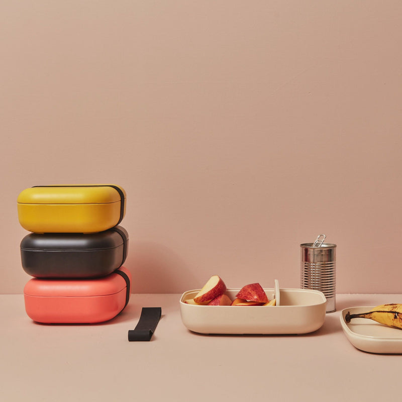 A stack of pink, black and yellow bento boxes sit on the left side, while in the center we see the white bento box, filled with a bounty of sliced apples. The lid lays on the foreground of the minimalist, modern set, with an aluminum can of soda or apple juice or some other beverage behind the bento box, and the stretchy band that holds the bento box together to the left of the white bento box in the center.