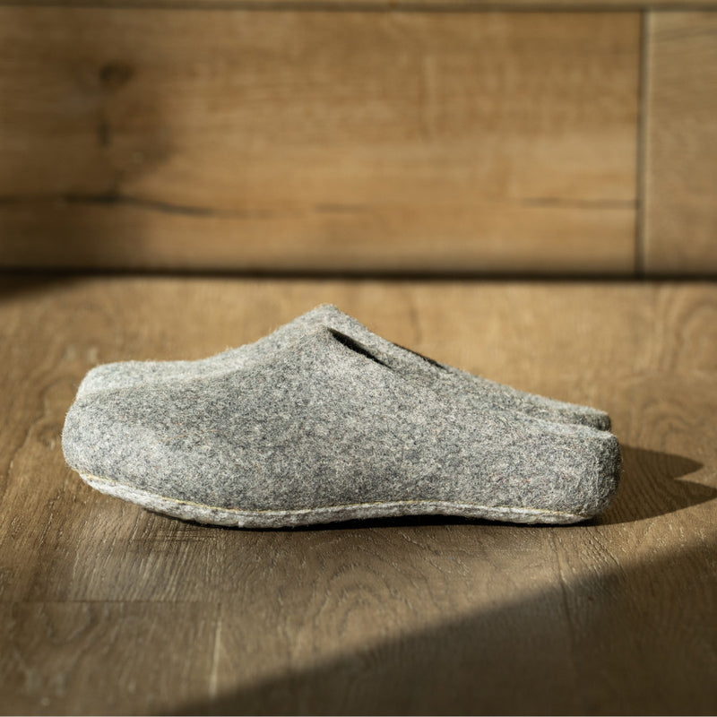 A pair of men's felted wool slippers in grey are set against an entirely wooden background; the slippers are seen from their side profile. Made from low-impact dye, these slippers are both beautiful, climate neutral, and made by craftsmen and women who are paid competitively.