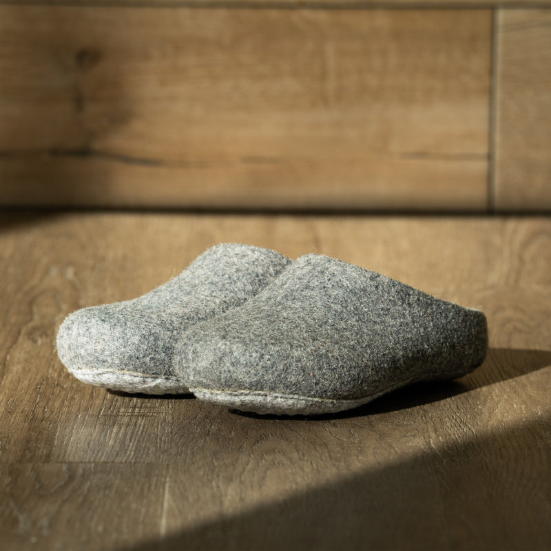 A pair of men's felted wool slippers are seen from a slightly tilted angle. The organic form and comfortable shape of the slippers is clear while the grey color stands against a light grey backdrop.