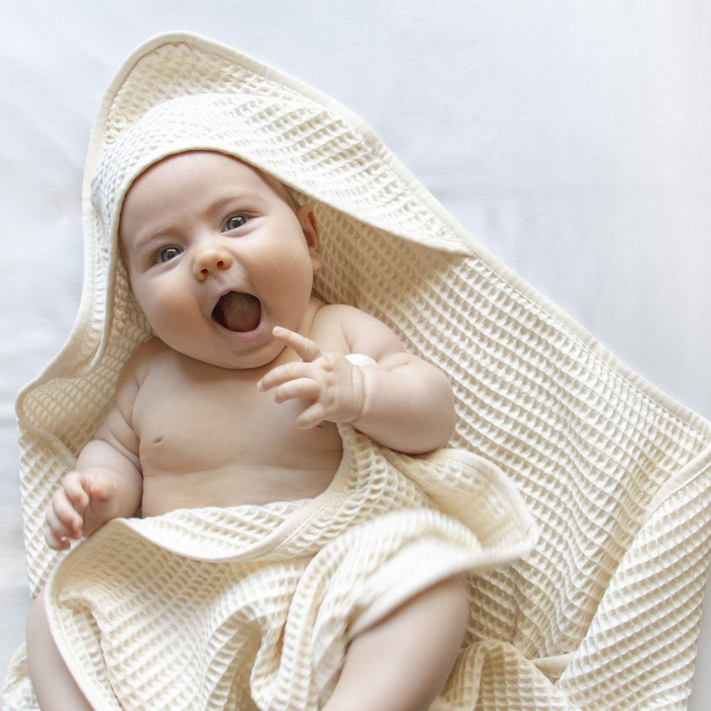 Extremely cute, pudgy baby is gingerly wrapped in a sustainable, hooded waffle towel bathrobe and is laughing and smiling.