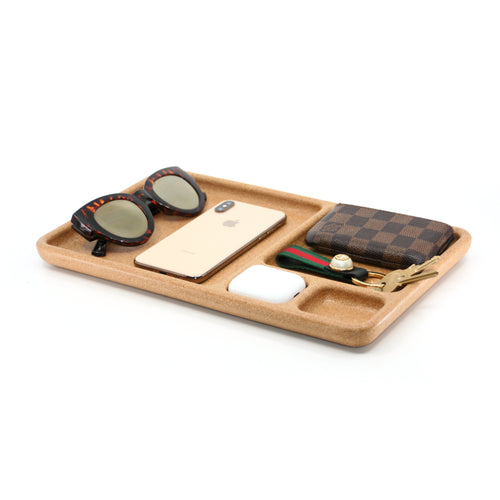 Rectangular cork, organizer tray made from recycled, eco-friendly materials. Large space on the left placed with tortoise shell over-sized sunglasses, and a rose gold iPhone 10 placed face down. 3 smaller compartments on the right side of the tray. One placed with a Louis Vuitton wallet and Gucci key chain with 2 keys hanging off the edge, another with the perfect pocket for your AirPods and the other open for your next pair of AirPods.