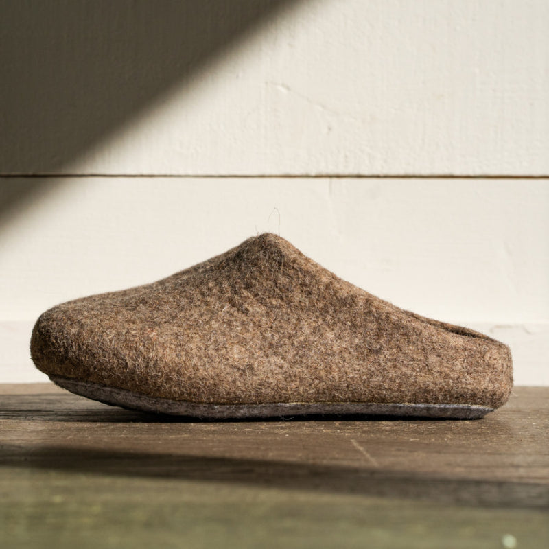 A singular men's felted wool house shoe sits in this frame. The shoe is set against a light grey wall while sitting on a dark wood floor. Made from only four materials, these house slippers are made from responsibly sourced wool and low impact dye.