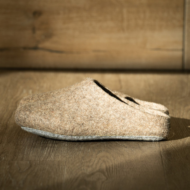 A pair of men's felted wool slippers in oatmeal sit against a plain wood background. These slippers are moisture-wicking, odor-resistant, and are made from only four materials! Even cooler, these slippers are made from thousands of years of traditions.