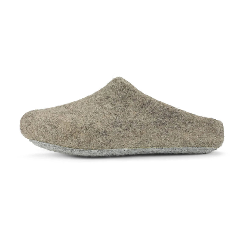A single men's felted wool slippers in oatmeal are alone in a plain white frame. The oat slippers are organic in shape, sustainably made, and incredibly comfortable.
