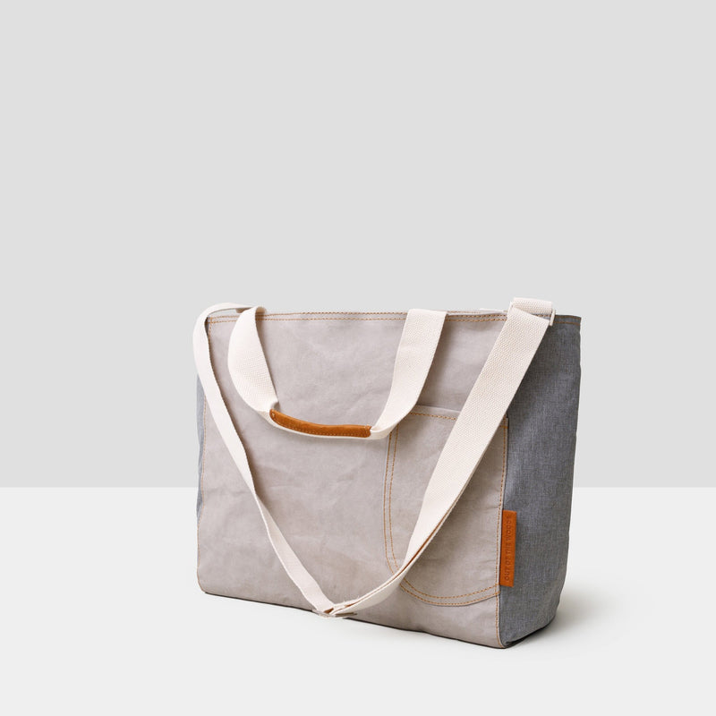 A large light grey cooler tote bag sits on a grey background. It has cream colored straps that are shown hanging down and saddle brown accents at the top handles. There is a cream colored long adjustable shoulder strap as well. There is a front open pocket on the front right side of the bag. The bag is sustainable and made from paper. It is both handsome and chic -- the perfect accompaniment to a park or beach picnic!