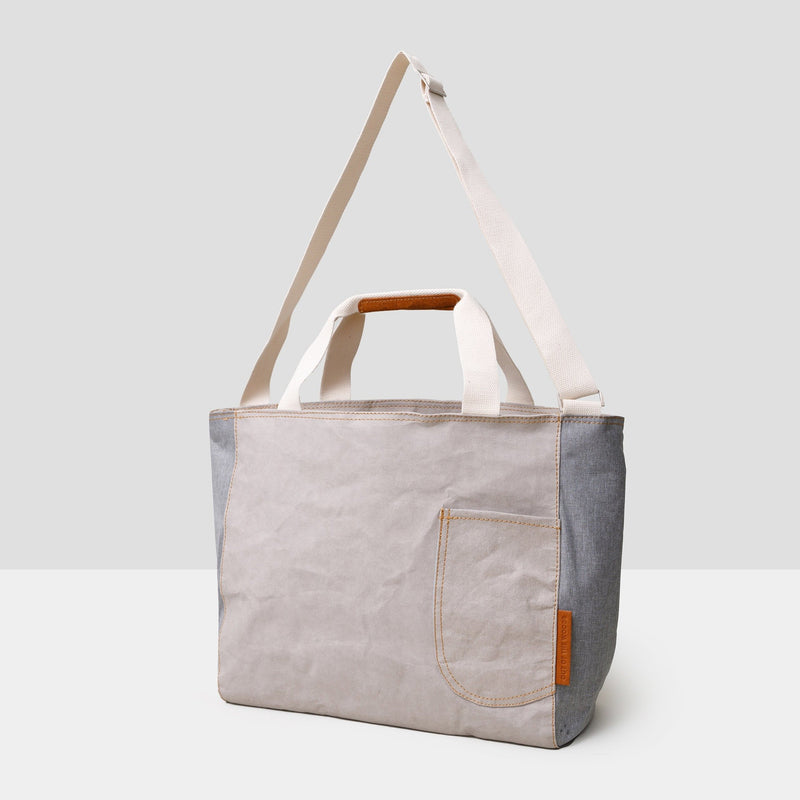 A large light grey cooler tote bag sits on a grey background. It has cream colored straps and saddle brown accents at the top handles. There is a cream colored long adjustable shoulder strap as well. All handles are shown floating and extended above the bag. There is a front open pocket on the front right side of the bag. The bag is sustainable and made from paper. It is both handsome and chic -- the perfect accompaniment to a park or beach picnic!