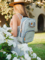 A grey cooler backpack (made sustainably from paper!) is shown on the back of a woman in a breezy dress and straw hat. She is standing in a park or garden. The bag is zipped closed but full of snacks for her picnic.