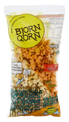 The spicy BjornQorn sun-popped corn bag has the same green/yellow logo with the addition of organic / squiggly lines surrounding it. It has a row of corn stalks on the bottom left hand-side but then depicts two birds wearing hats enjoying the sun on the bottom right hand side.