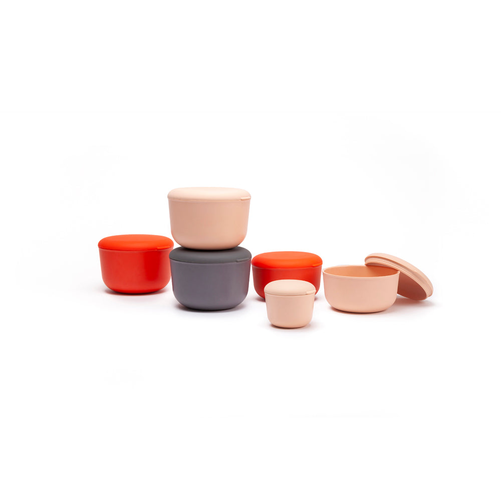 Six sustainable bento box snacking containers made of sustainable bamboo are stacked upon each other and organized neatly in front of a white background.