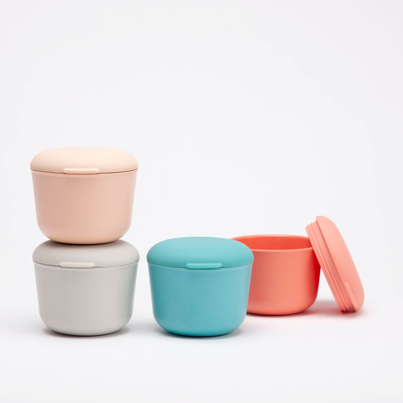 On the left, in front of a white background, a grey bamboo sustainable food storage container is stacked beneath an identical blush colored one. To its right is a teal blue container, also sealed, and in the background behind that bento box is coral colored one, whose lid is leaning up against its side, showing the screw top and soft lid detail, perfect for kids lunches or snacks.