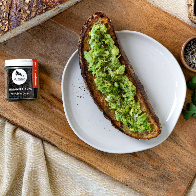 A long piece of toast sits on top of a wood cutting board. She's covered in mashed avocado, scallions and seaweed flakes. A jar of seaweed flakes sits to the left.