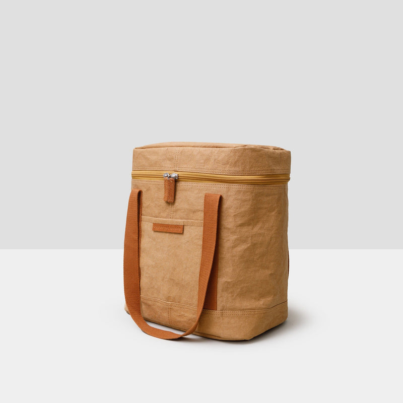 A saddle brown rectangular cooler bag sits on a grey background. It has darker brown straps that are hanging down and a full zipper top with two hanging zippers. There is a large open front pocket, too. The bag is sustainable and made from paper. It is both handsome and chic -- the perfect accompaniment to a park or beach picnic!