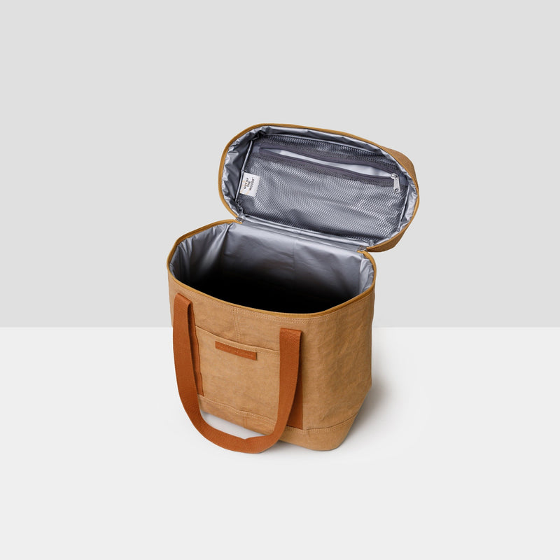 A saddle brown rectangular cooler bag sits on a grey background. It has darker brown straps that are hanging down and a full zipper top with two hanging zippers. The bag is shown with the zip top fully open. You can see the metallic cooler material inside the bag. In the interior of the top lid, there is a netted zipper pocket for convenience. The bag is sustainable and made from paper. It is both handsome and chic -- the perfect accompaniment to a park or beach picnic!