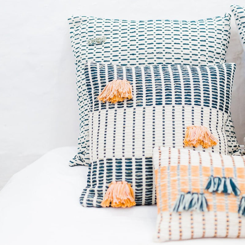 The bright organic cotton pillow is stacked with two other vibrant and colorful pillows. The Salento Pillow is in the middle.